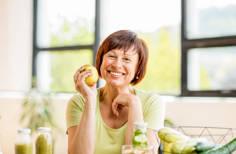 middle aged woman holding apple smiling