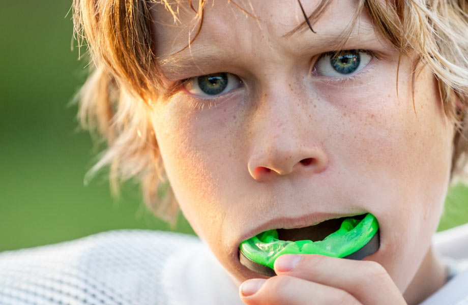 Young football player with green mouthguard