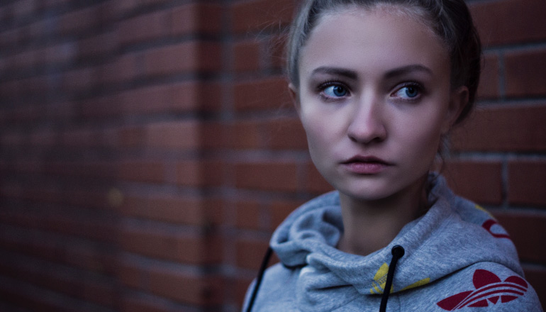 Blonde young woman wears a gray Adidas sweatshirt and stands by a red brick wall while worrying about her inflamed gums