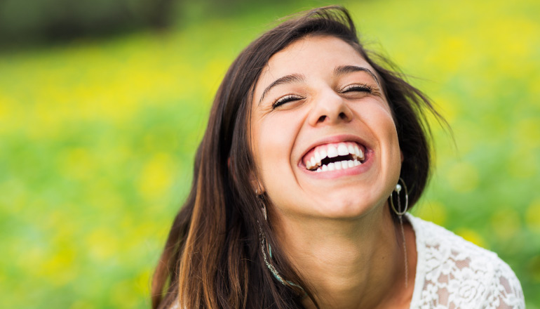 Closeup of a brunette young woman in a green field with flowers smiling with her eyes closed