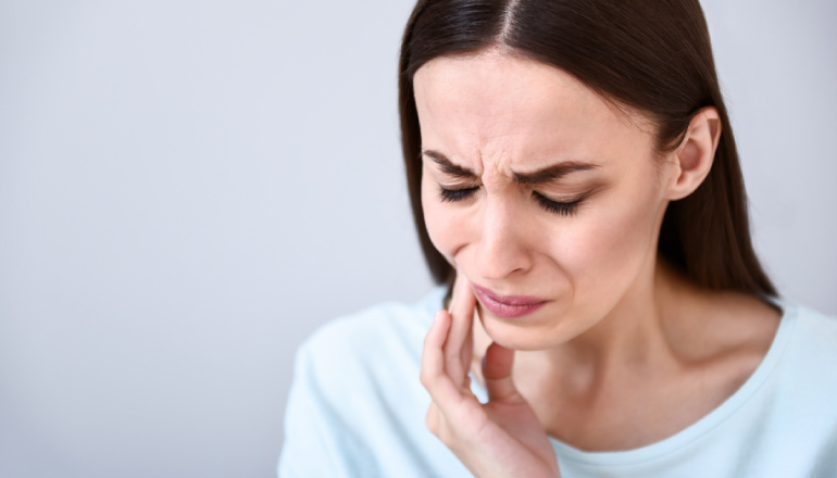 Brunette woman wearing a light blue shirt cringes and touches her cheek due to pain from sensitive teeth