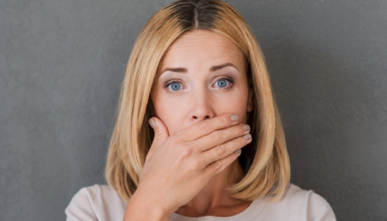 woman covers her mouth to hide gum disease