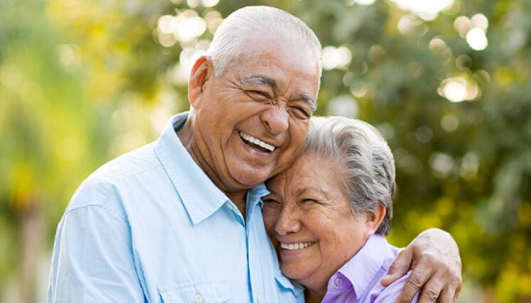 senior couple hug and smile after getting dentures